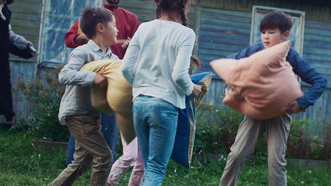 Children fight pillows in yard of country house. Flying feathers. Men in costume Footage