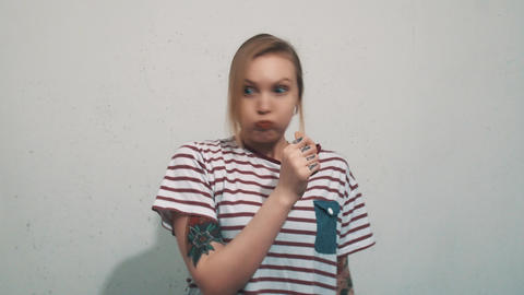 Joyful blonde woman in striped shirt with tattoos blow cheeks up on white wall Live Action