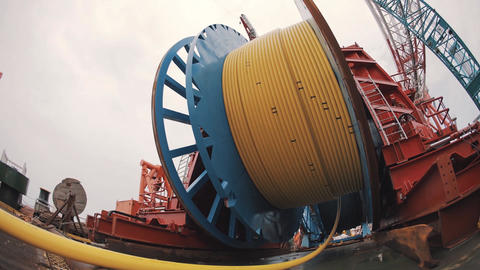 Timelapse massive metal wheel roll and unroll long yellow hose, day night change Footage
