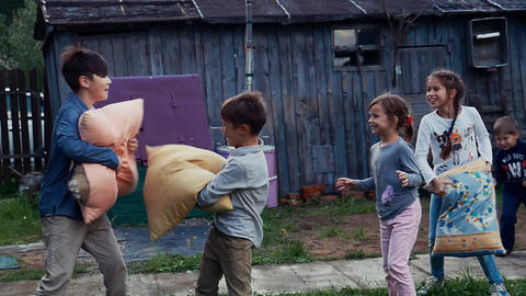 Kids fight pillows in yard of country house. Countryside. Entertainment. Fun Footage