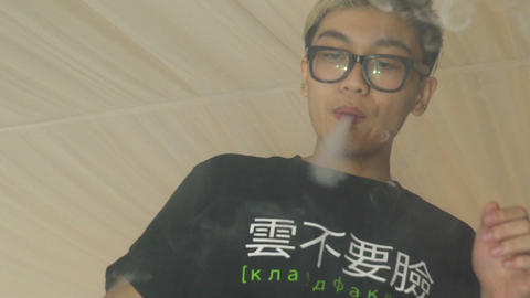 Asian boy in glasses make clouds from electronic cigarette steam. Vaper. Smoking Footage