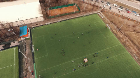 Aerial shot of sportsmen playing soccer on green grass field on summer day Footage