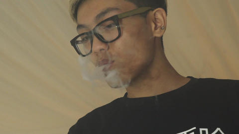 Asian boy in glasses exhale steam from electronic cigarette. Vaper. Smoker Live Action
