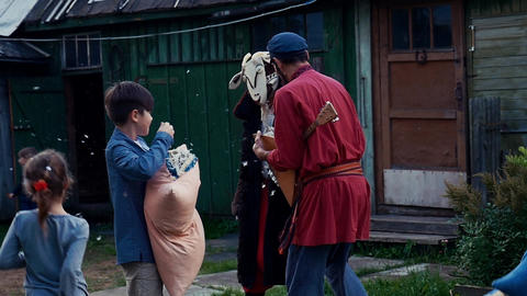 Man with balalaika give man feathers from pillow in yard of country house. Kids Footage