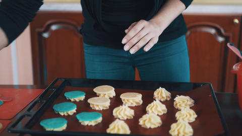 Confectioner woman puts beige dough circles on cream piles on baking pan Footage