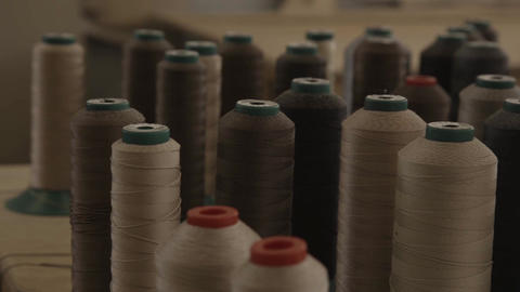View of many long coils with brown and beige threads Live Action
