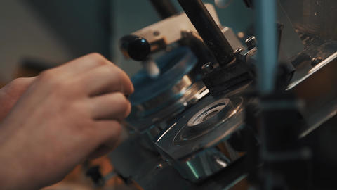 Male hands assembles precise lense measuring machine with circular markings Footage