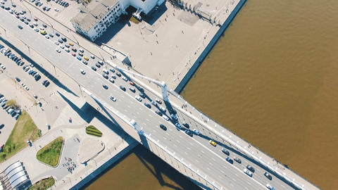 Bird eye view of city river, road traffic on concrete bridge, boats in water Footage