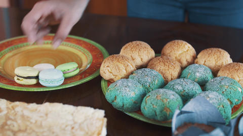 Female confectioner hands places colorful macarons on plate upon table Footage
