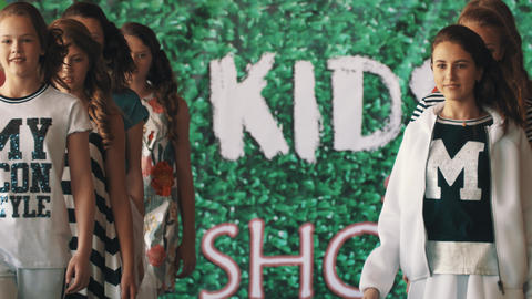 Young girls models showing clothes walking on catwalk at kids fashion show Footage
