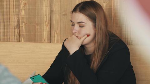 Fat woman rest face on fist using smartphone in recreational indoor area Footage