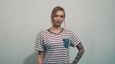 Pretty tattoed blonde girl in striped shirt, have idea and pull up finger Live Action