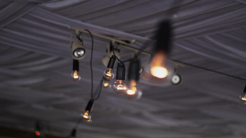 View of lighted light bulbs in terrace of summer restaurant. Sparkle Footage