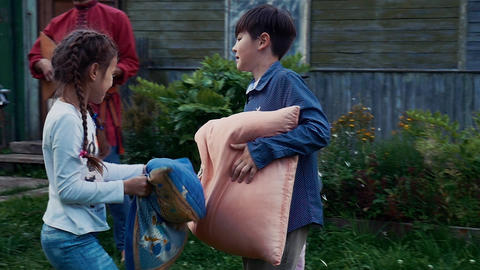 Kids fight pillows in yard of country house. Countryside. Entertainment. Men Footage