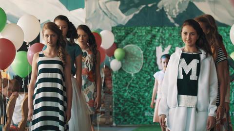 Young joyful girls models walking on podium at kids fashion show Live Action