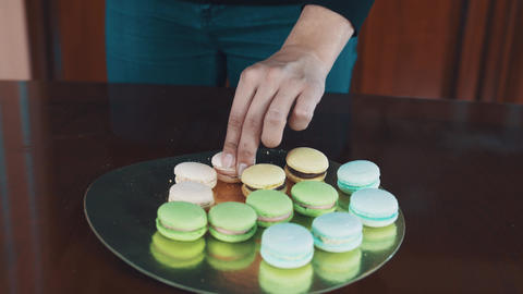 Pastry cook woman hands squeezes strawberry buttercreme filling making macaron Footage