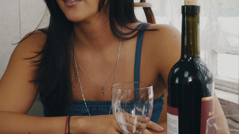 Brunette girl chatting at table with wine bottle on terrace of country house Footage