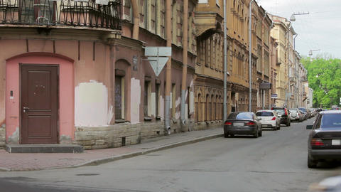 View of a street corner with road signs, people and cars in summer evening Footage