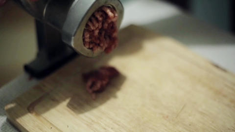 Process of grinding fresh meat on wooden kitchen board by aluminum meat grinder Footage