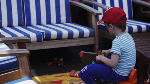 Little boys with painted face play with toys at terrace of restaurant. Summer Footage