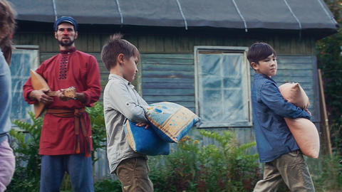 Two boys fight pillows in yard of country house. Childhood. Man play balalaika Footage