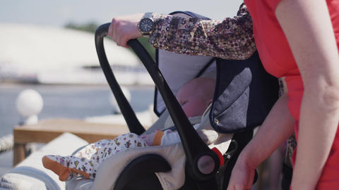 Parents stay on street with cute baby boy in baby carriage. Family. Summer Footage