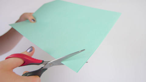 Corner being cut off a blue piece of paper Footage