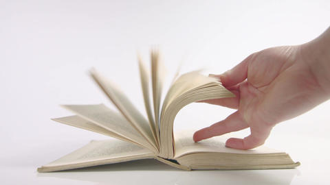 Hand flicking through old book on a white background Live Action