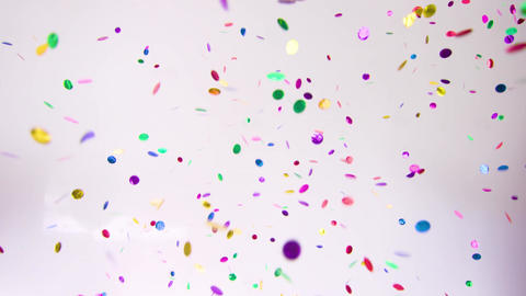 Multi coloured confetti from two confetti cannons on a white background Live Action