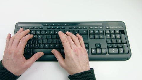 Overhead shot of a mans hand typing on a black keyboard Footage