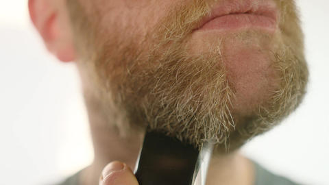 Close up of a man shaving off a beard Footage