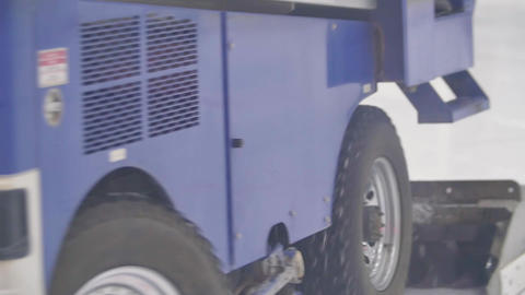 Big blue ice resurfacer truck polishes ice rink Live Action
