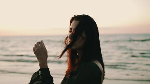 Girl in dark dress pose to photographer on beach. Photoshoot. Sea. Sunset. Model Footage