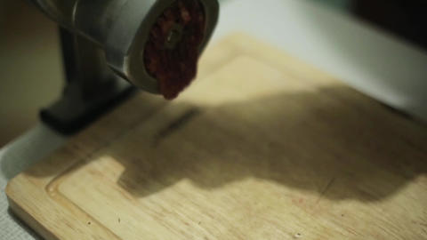 Process of grinding fresh meat on wooden kitchen board by old meat grinder Footage