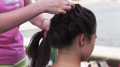 Woman in pink shirt weaving braid to young brunette girl. Hairstyle. Summer Footage