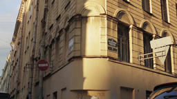 View of a corner building on a street in summer sunny evening. Pan horizontal Footage