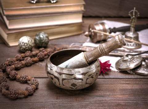 a copper singing bowl and a wooden stick フォト