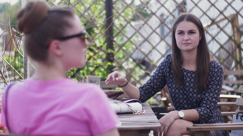 Young girls sit on terrace of restaurant. Speaking. Friends. Relax. Holidays Footage