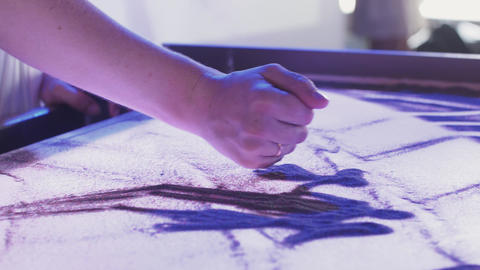 View of young woman drawing beautiful picture of family by sand. Art. Lighting Footage