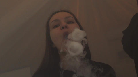 Girl exhale steam circles from electronic cigarette. Vaper. Subculture. Smoker Live Action