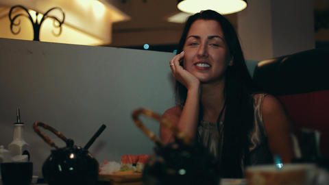 Brunette girl sit at table in sushi restaurant. Laughing. Talk with someone Footage