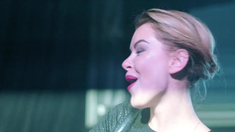 Attractive Dj girl in black top mixing, smile, singing at turntable in nightclub Footage