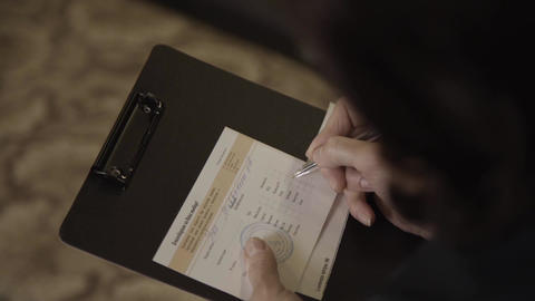 Womans hands holds a black folder and fills a document on it Footage
