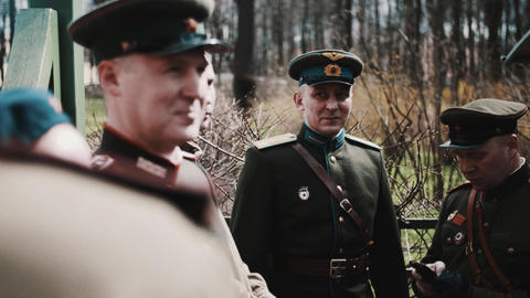 Group of men in soviet soldiers outfits talking and joking in ci Footage