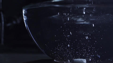 Tree sugar cubes fall into a glass cup with water, slow motion video Footage