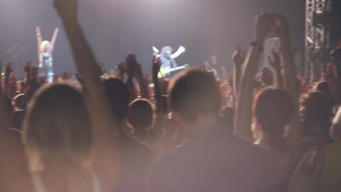 People raise hands on rock concert in nightclub. Band performing on stage Footage