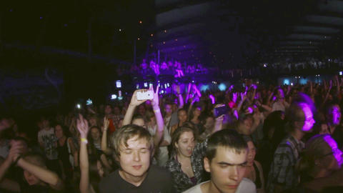 Many people raise hands on concert in crowded nightclub. Clapping. Spotlights Footage
