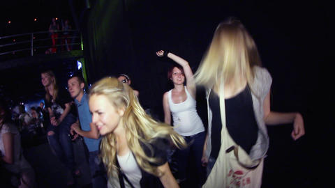 Two young girls clapping in crowded nightclub at rock party. Illumination Footage