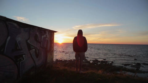Back side of boy watcching summer sea sunset. Alone. Freedom, relax, meditation Footage