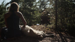 Back side of girl scratching a big dog in forest. Summer sunny day. Slow motion ビデオ